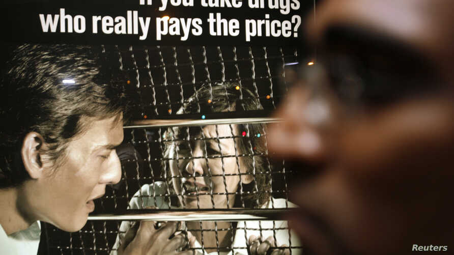 Human rights lawyer M. Ravi stands in front of a drug prevention advertisement during a vigil for Nigerian Iwuchukwu Amara Tochi outside the Singapore Changi Prison, Jan. 25, 2007.