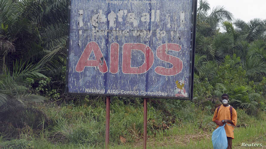 FILE - A man stands next to an AIDS billboard as he cleans a street in Yaounde, March 20, 2009.