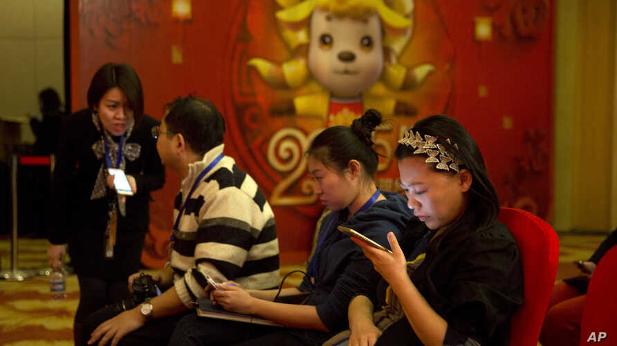 FILE - In this photo taken Feb. 2, 2015, a woman browses her smartphone near other attendees at a press conference in Beijing. China announced on Feb 4. 2015 that users of blogs and chat rooms will be required to register their names with operators a