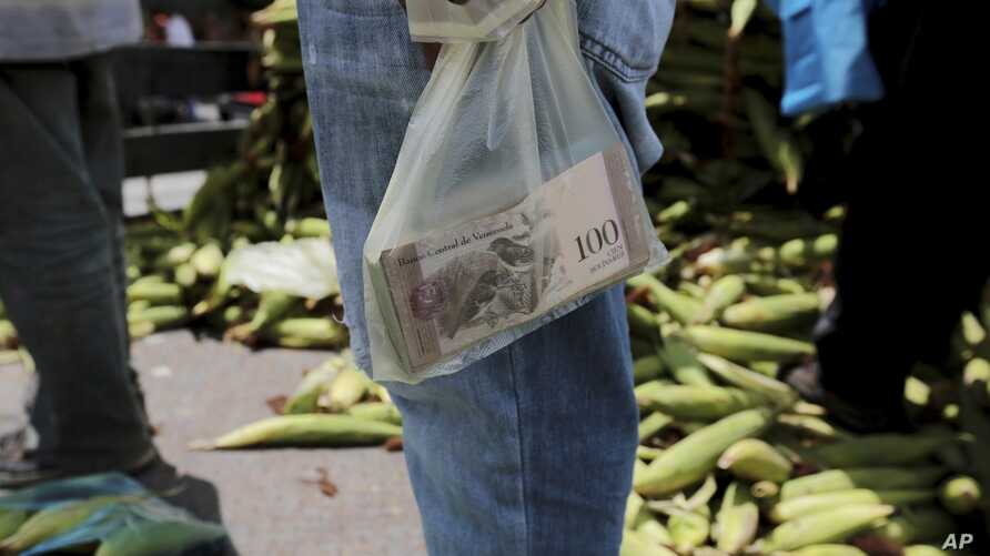 A vendor holds the bank notes in a plastic bag, at a market in Caracas, Venezuela, Sept. 23, 2017.