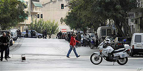 A police explosive expert, left, prepares a controlled blast of a suspicious package at a private delivery company in Athens, 02 Nov 2010