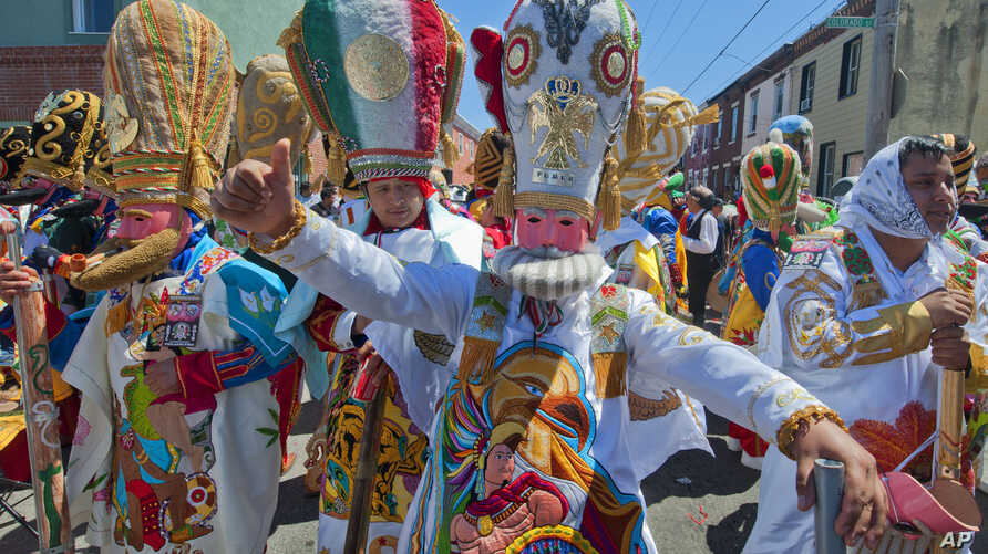 FILE - Marchers in Philadelphia's El Carnaval de Puebla en Filadelfia don costumes depicting the Mexican army that prevailed over the French and Turkish forces during the 1862 Battle of Puebla, commonly known as Cinco de Mayo.
