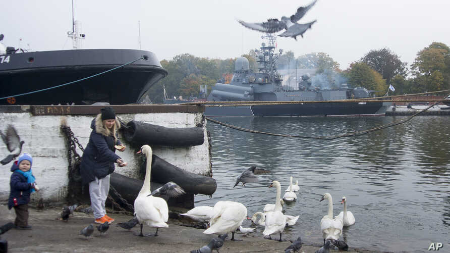 Olga Zyukina and her son Yura feed swans on the pier at the Russian Baltic Fleet base of Baltiysk, Russia, Oct. 19, 2016. Despite mounting tensions between Russia and NATO, Russians seem largely oblivious to a threat of a new Cold War.