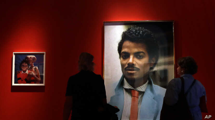 Visitors look at an artwork by Hank Willis Thomas on display at the Michael Jackson: On The Wall exhibition at the National Portrait Gallery in London, June 27, 2018.