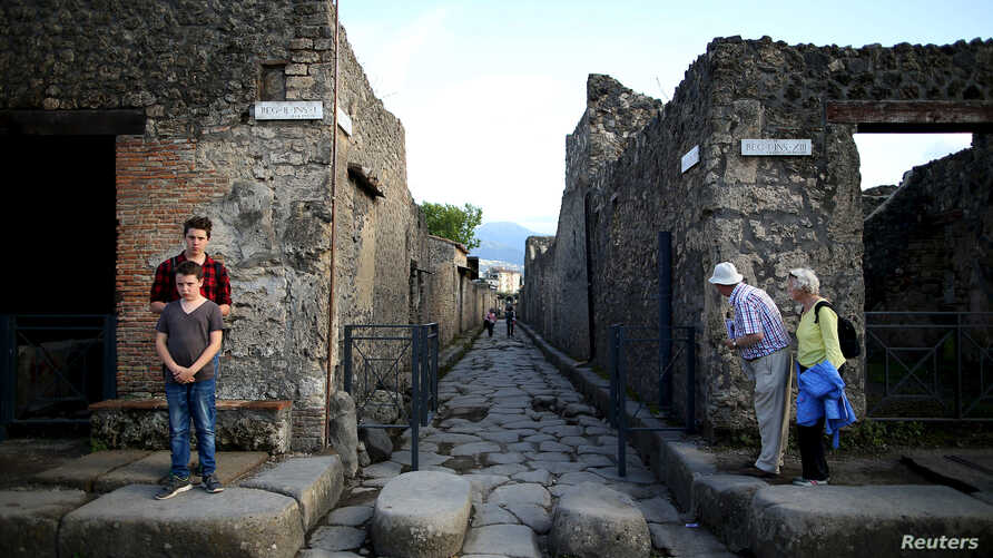FILE - Tourists look down an ancient Roman cobbled street at the UNESCO World Heritage site of Pompeii, Italy.