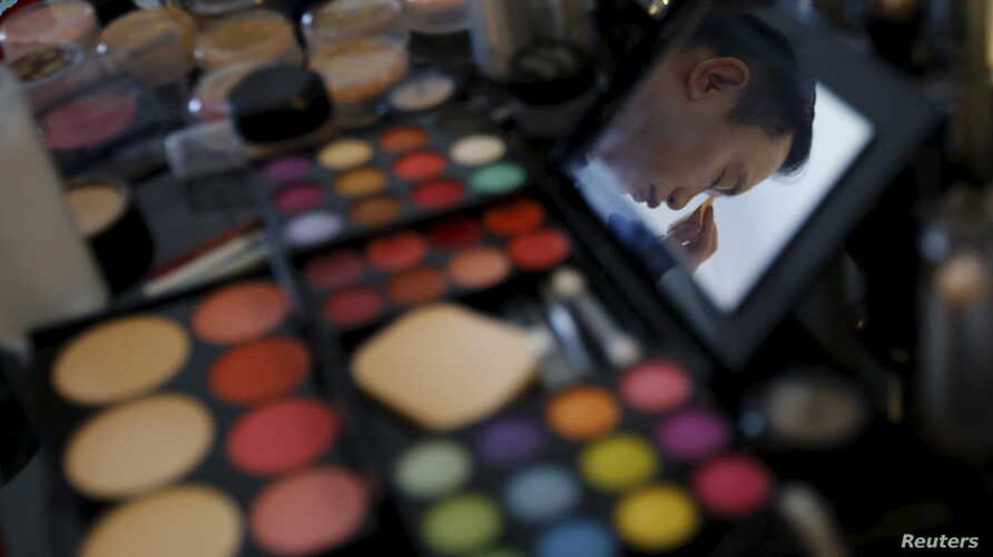 """FILE - A man is reflected on a mirror as he does his make-up before giving a performance at the """"Divas in Paradise"""" themed party organized by Beijing LGBT Center at the W Hotel Chang'an in Beijing, China."""