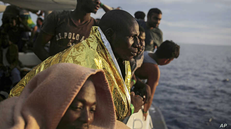 Migrants look out from the deck of the Spanish NGO ProActiva Open Arms vessel as they wait to reach the Italian coast on the Mediterranean Sea a day after being rescued off the Libyan coast, Sept. 7, 2017.