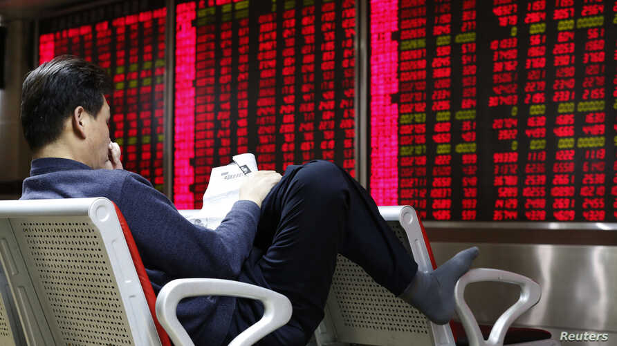 An investor reads a newspaper in front of an electronic board showing stock information at a brokerage house in Beijing, China, Feb. 16, 2016.