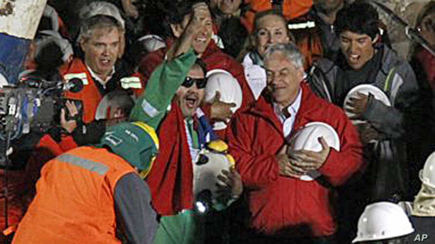 Miner Luis Urzua, the last miner to be rescued, center wearing green, celebrates next to Chile's President Sebastian Pinera after being rescued from a collapsed gold and copper mine, 13 Oct 2010