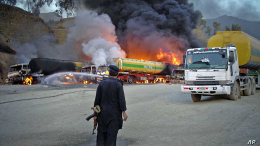 A security official stands near oil tankers - carrying fuel to US-led NATO forces in the northwestern tribal region of Khyber - that were set ablaze by a bomb blast near the main border crossing of Torkham, on the outskirts of Landikotal in Afghanist
