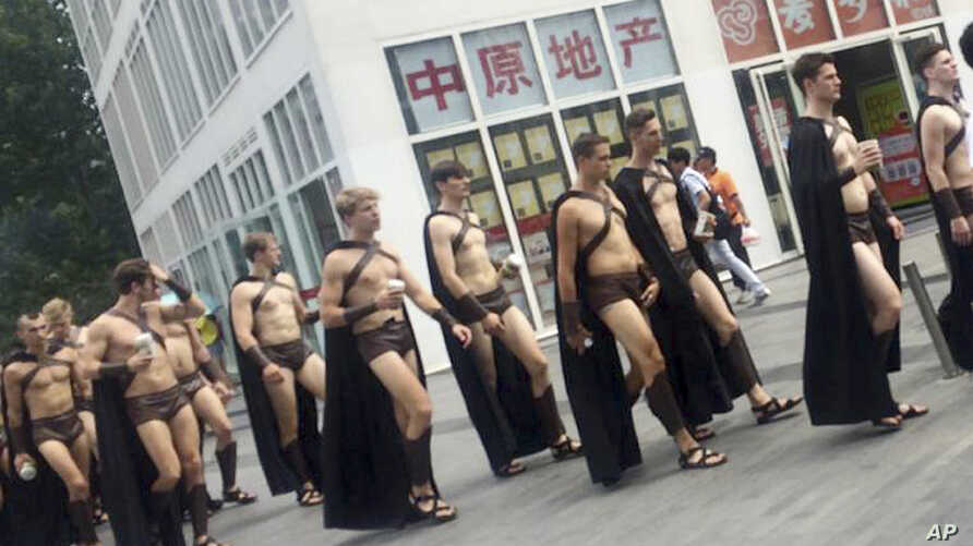 Men dressed in Spartan-style costumes walk through a commercial plaza in Beijing, July 22, 2015.