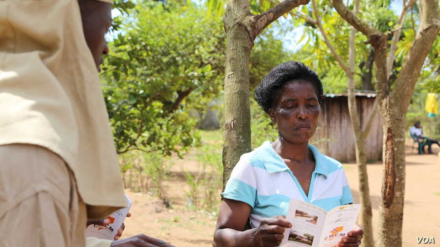 Information teams are chosen from the communities to disseminate information about residual spraying. They go door-to-door explaining the process and when it will take place, Mozambique, Nov. 13, 2014. (Gillian Parker/VOA)