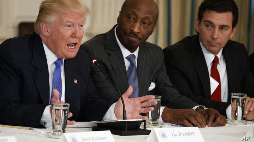 FILE - In this Feb. 23, 2017 photo, President Donald Trump, left, speaks during a meeting with manufacturing executives, including Merck CEO Kenneth Frazier, center, and Ford CEO Mark Fields. Frazier is resigning from the President's American Manufac