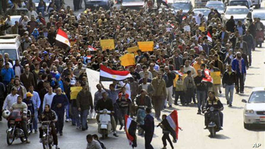 Anti-government protesters march through a street in Cairo, Egypt. Egypt's military threw its weight Friday behind President Hosni Mubarak's plan to stay in office through September elections, February 11, 2011.