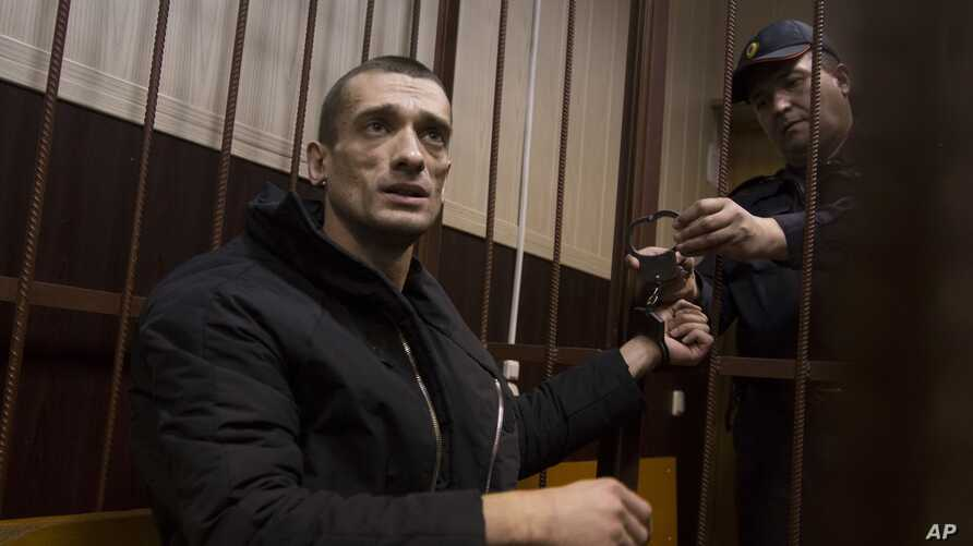 FILE - Russian artist Petr Pavlensky speaks to journalists as he sits in a cage in courtroom in Moscow, March 31, 2016. The artist, known for his political art performances, is one of three winners of the Human Rights Foundation's 2016 Vaclav Havel P