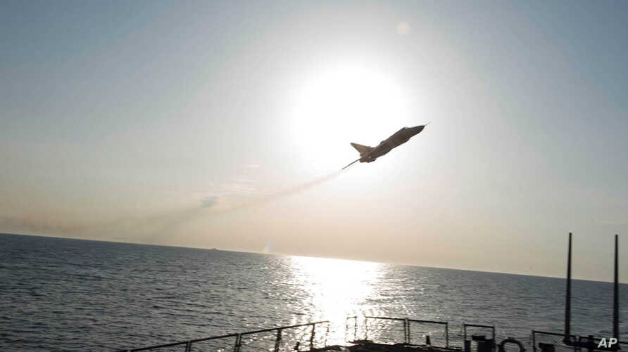 In this photo provided by the U.S. Navy, a Russian Sukhoi Su-24 attack aircraft makes a low altitude pass by the USS Donald Cook in the Baltic Sea, April 12, 2016.