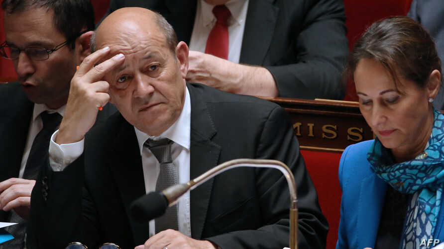 French Defence Minister Jean-Yves Le Drian (L) and French Environment and Energy Minister Segolene Royal attend a session of questions to the government at the National Assembly, on May 07, 2014 in Paris.
