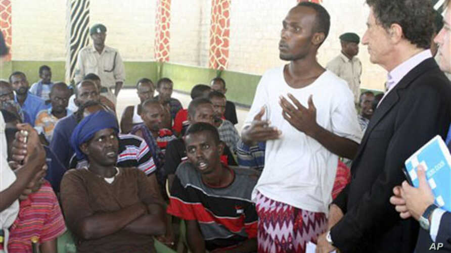 The United Nations Secretary General's special advisor on piracy legal issues Jack Lang, from France, right, listens to an unidentified suspected Somali pirate, on remand, at the Shimo la Tewa GK Prison in Mombasa, Kenya, 11 Oct 2010