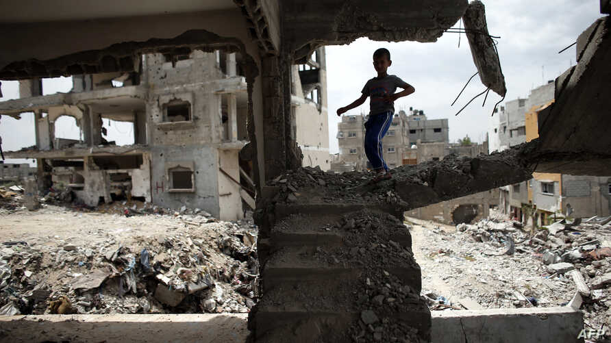 A Palestinian boy plays amid the rubble of his familiy's former house which was destroyed during the 50-day war between Israel and Hamas militants in the summer of 2014, in the Eastern Gaza City Shujaiya neighborhood, May 11, 2015,.