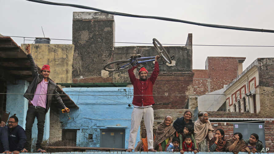 FILE - A supporter lifts a bicycle, the party symbol of the Samajwadi Party (SP), during a joint election campaign rally by Uttar Pradesh state.