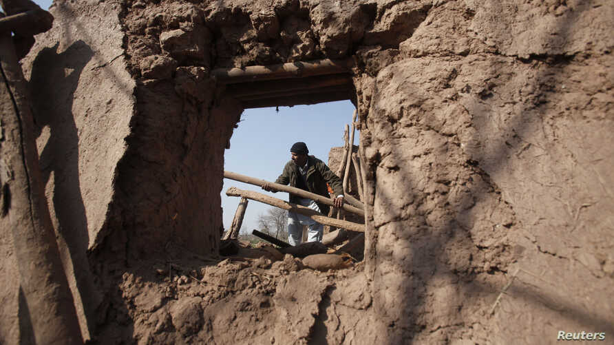 A resident collects items from the rubble of a house after it was damaged by grenades from gunmen on the outskirts of the northwestern city of Peshawar, Pakistan, Feb. 12, 2014.