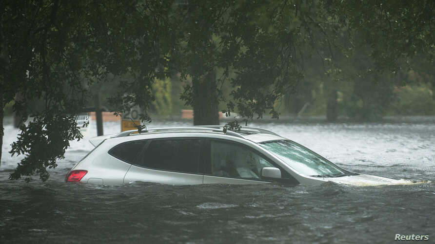 A vehicle is submerged in flood waters in Jourdan River Shores neighborhood as Hurricane Isaac passes through Kiln, Mississippi, August 29, 2012.