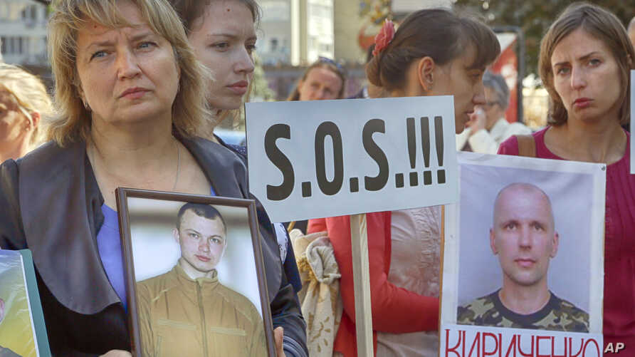 Relatives of the Ukrainian prisoners of war hold their portraits at a rally outside the German embassy in Kyiv, Ukraine, Sept. 14, 2016.