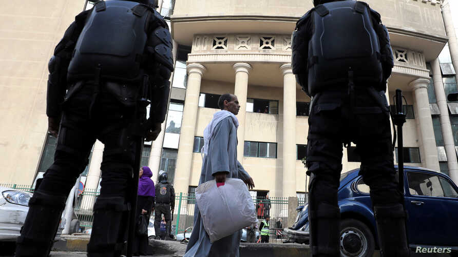 Egyptian security forces stand guard outside the court during the trial of human rights lawyer and ex-presidential candidate, Khaled Ali in Cairo, Jan. 3, 2018.