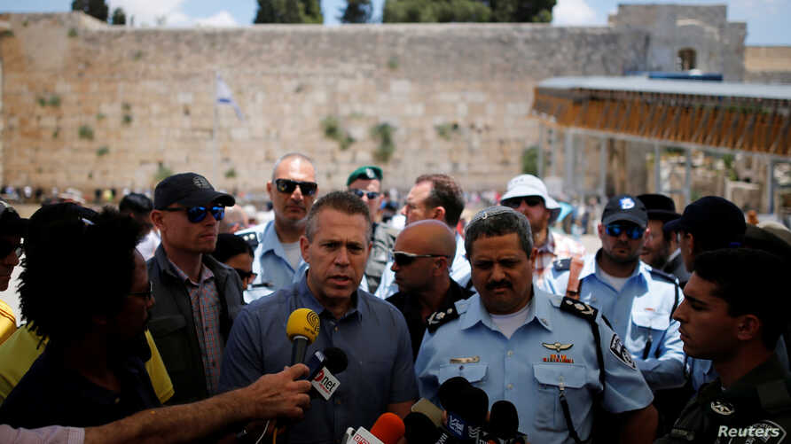 FILE - Israel's Public Security Minister Gilad Erdan, third from left, and police commissioner Roni Alsheich, third from right, speak to members of the media at the Western Wall in Jerusalem's Old City, June 10, 2016.