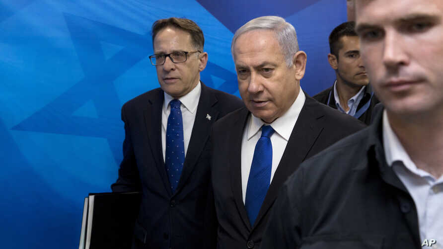 FILE - Israeli Prime Minister Benjamin Netanyahu, center, arrives with Cabinet Secretary Tzachi Braverman for a weekly cabinet meeting at the prime minister's office in Jerusalem, April 29, 2018. Israeli media said Tuesday that the meetings have been