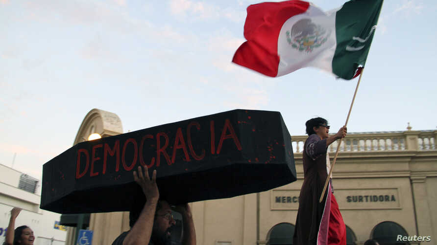 A protester holds a symbolic coffin who reads 'democracy' during a demonstration in support of Andres Manuel Lopez Obrador, runner-up in Mexico's presidential race, after a court threw out his challenge to the poll result, in Hermosillo, Sept. 1, 201