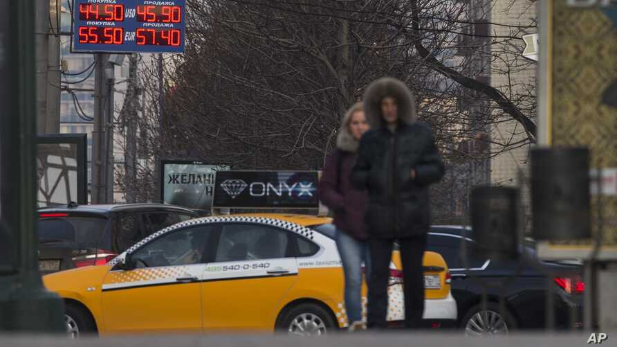 People pass by a display with exchange rates in downtown Moscow on Monday, Nov. 10, 2014.