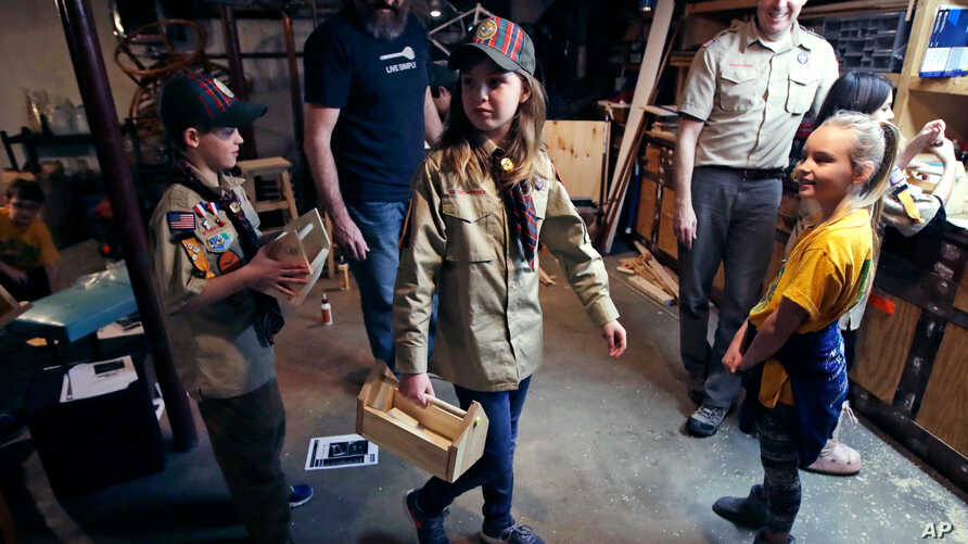 """FILE - Tatum Weir, center, carries a tool box she built as her twin brother Ian, left, follows after a Cub Scout meeting in Madbury, N.H., March 1, 2018. Fifteen communities in New Hampshire are part of an """"early adopter"""" program to allow girls to be"""