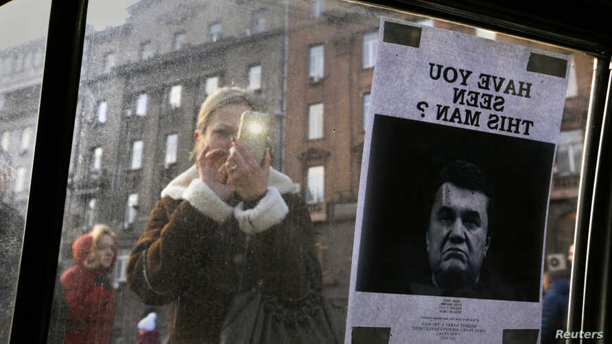 "A woman takes a photo of a ""Wanted"" notice for fugitive Ukrainian president Viktor Yanukovich, plastered on the window of a car near Kyiv's Independence Square Feb. 24, 2014."