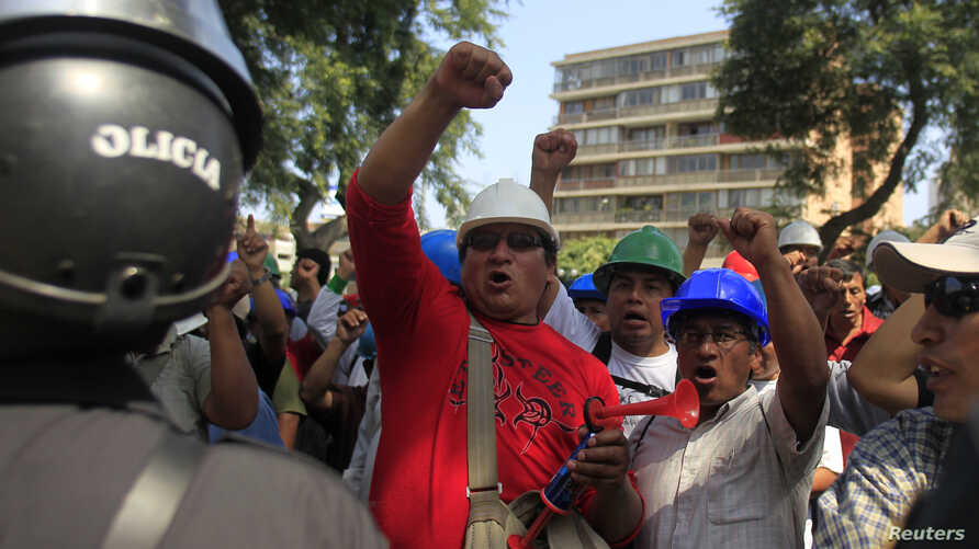 FILE - Mining workers of Doe Run Peru smelter protest in front of the Labor ministry in Lima to demand that Peru's government save their jobs at the shuttered La Oroya metals smelter in the Andes, April 19, 2012.