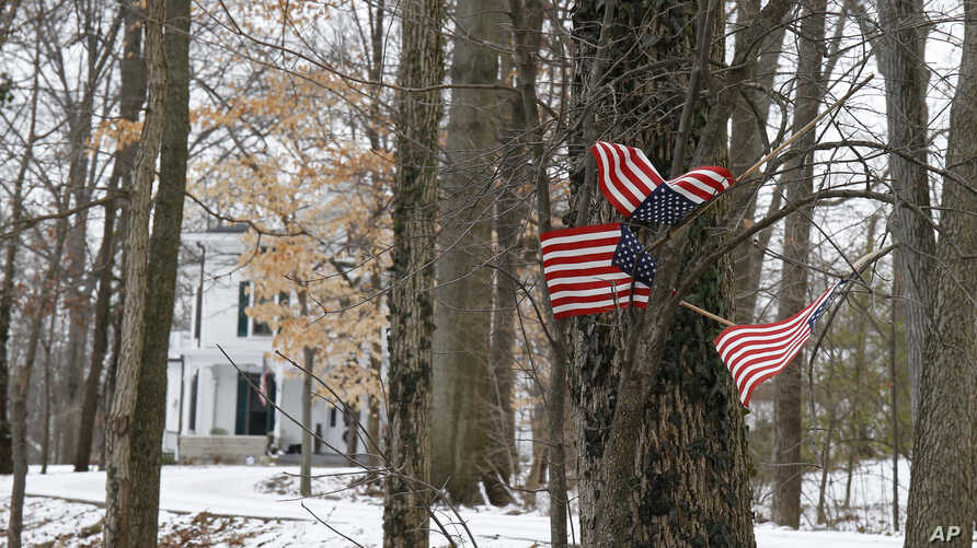 "Small American flags have been placed in the trees in front of the Warmbier family home, Friday, Jan. 22, 2016, in Wyoming, Ohio. North Korea on Friday announced the arrest of Otto Warmbier, a university student from Ohio, for what it called a ""hosti"