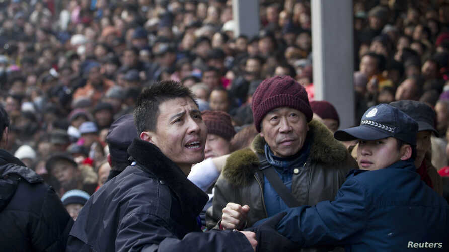 Security personnel try to control the crowd as locals visit the Lingyin Temple for free porridge distributed by the temple during the Laba Festival in Hangzhou, Zhejiang province January 19, 2013.