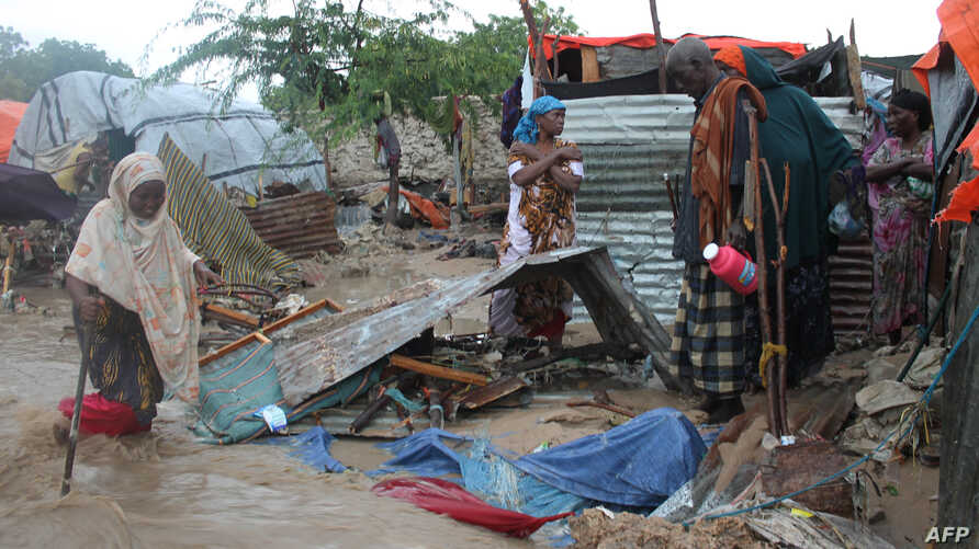 Members of a family stand next to their makeshift house that was swept at the internally displaced people (IDP) camp in Hodon district in Mogadishu, Somalia, May 30, 2015, following heavy rain that has pounded the parts of the country.