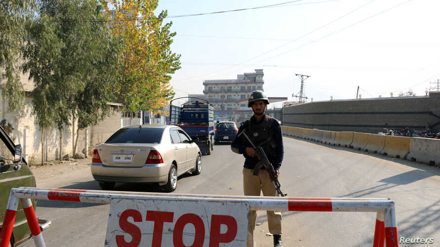 FILE - A policeman stands guard on a road in Mingora, in Swat Valley, Pakistan, Dec. 4, 2016. Saturday, a suicide bombing targeted army officials in a part of the scenic valley where members of the military conduct sports activities.