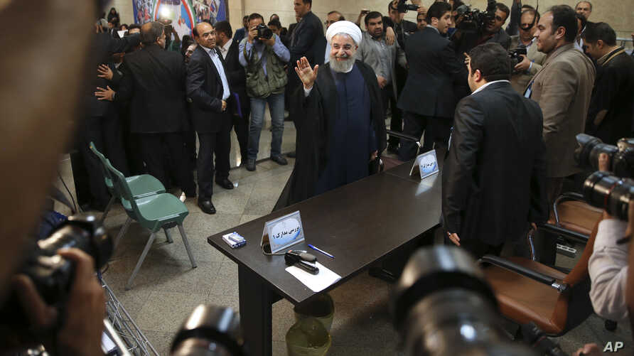 Iranian President Hassan Rouhani waves to media as he arrives at the Interior Ministry to register his candidacy for the May 19 presidential elections, in Tehran, Iran, April 14, 2017