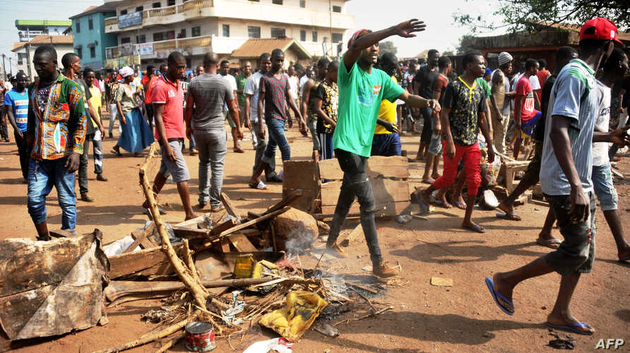People demonstrate in a street on Feb. 21, 2017, in Conakry where at least six people died during violent protests as people demonstrated over teachers' strikes that have closed schools for the past three weeks, government sources said.