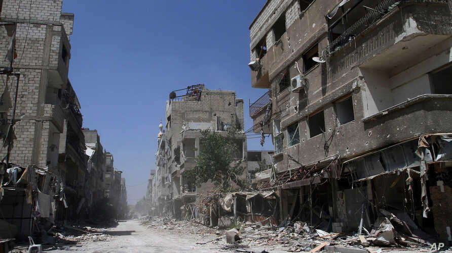 In this photo taken during a Syrian government-led media tour, buildings damaged during battles between Syrian troops and rebels stand along an empty street in Mleiha, about 10 kilometers (6 miles) southeast of downtown Damascus, Syria, Aug. 15, 2014