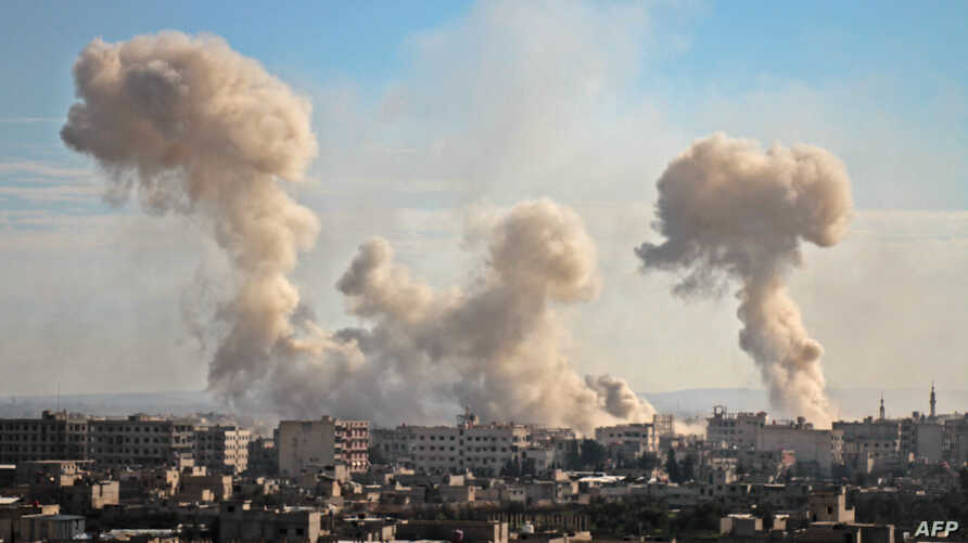 Smoke rises from buildings following bombardment on the village of Mesraba in the rebel-held besieged Eastern Ghouta region on the outskirts of the capital Damascus, Feb. 19, 2018.