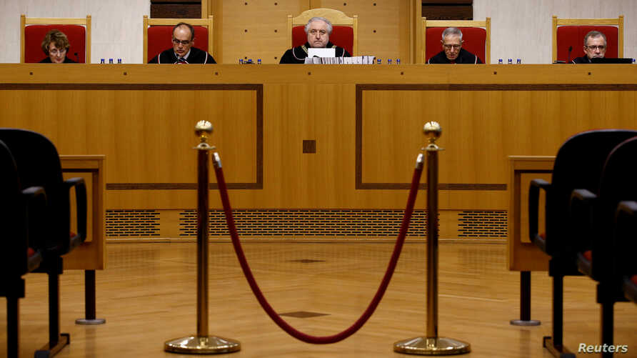 FILE - The head of Poland's Constitutional Court Andrzej Rzeplinski (C) and judges attend a session at the Constitutional Tribunal in Warsaw, Poland, April 6, 2016.