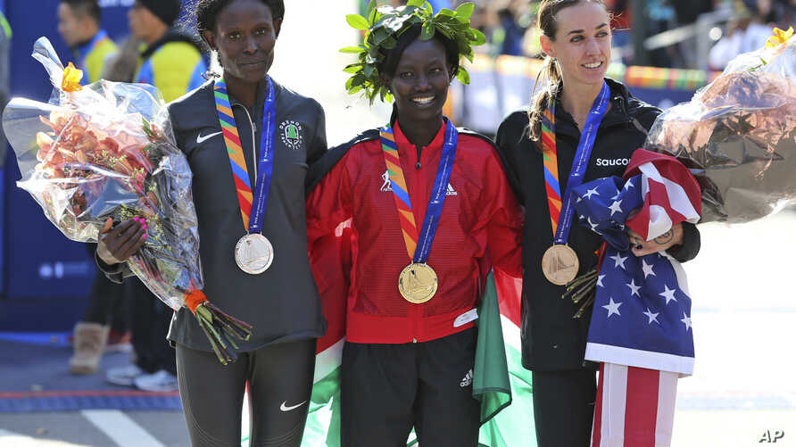 NYC Marathon: First place finisher Mary Keitany, of Kenya, center, second place Sally Kipyego, of Kenya, left, and third place Molly Huddle, of the United States, pose for a picture at the finish line of the 2016 New York City Marathon in New York, S