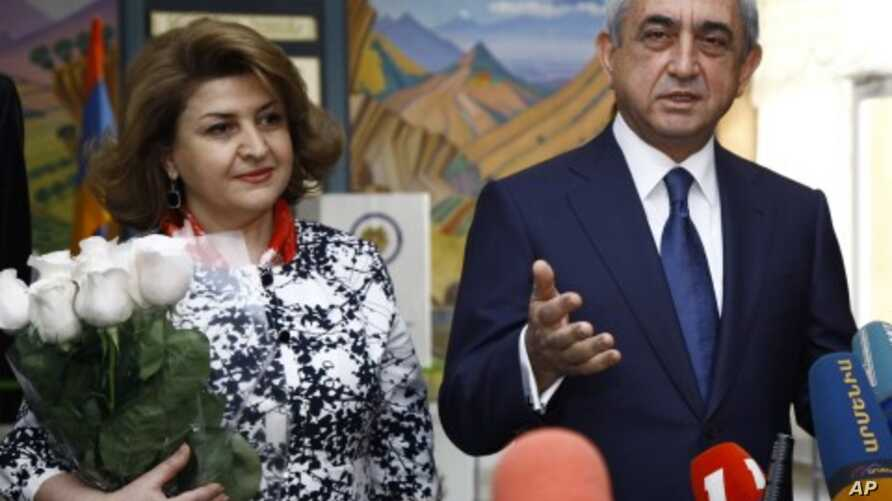 Armenian President and Republican Party President Serzh Sarkisian speaks to press after he voted during parliamentary elections in Yerevan, Armenia on Sunday, May 6, 2012. President's wife Rita Sarkisian smiles at left.