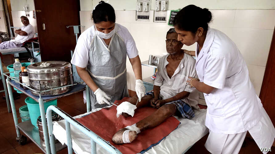 Nurses are dressing а wound on leprosy patient Gopal Bag, following amputation of his leg, at the Leprosy Mission Trust India hospital, Kolkata, Sept. 20 2016. (M. Hussain/VOA)