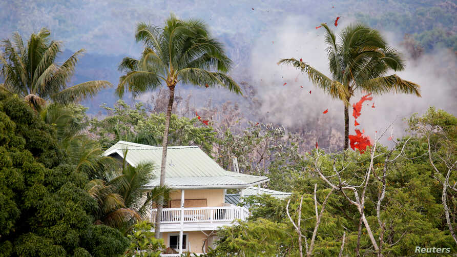 Smoke and lava erupt from a fissure near a home on the outskirts of Pahoa during ongoing eruptions of the Kilauea Volcano in Hawaii, May 14, 2018.