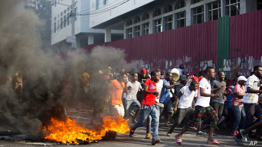 Demonstrators run away during a protest to demand the resignation of President Jovenel Moise and an explanation of how Petro Caribe funds have been used by the current and past administrations, in Port-au-Prince, Haiti, Feb. 9, 2019.