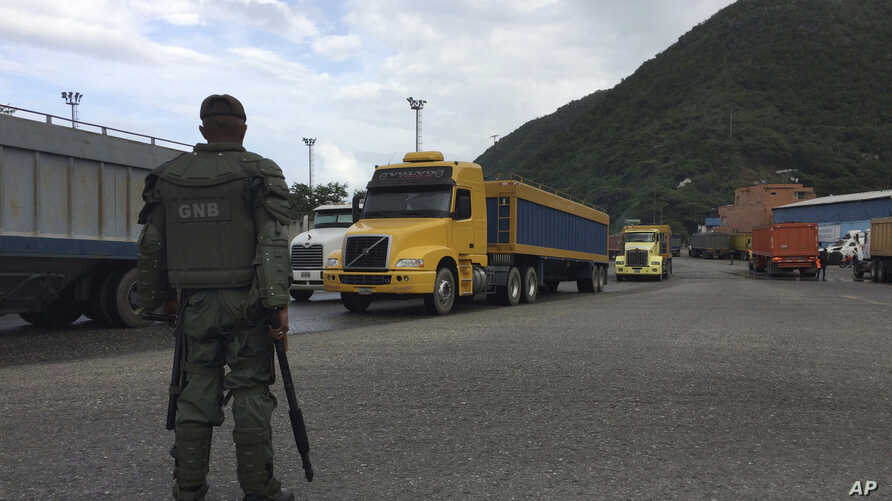 FILE – A National Guard soldier watches over cargo trucks